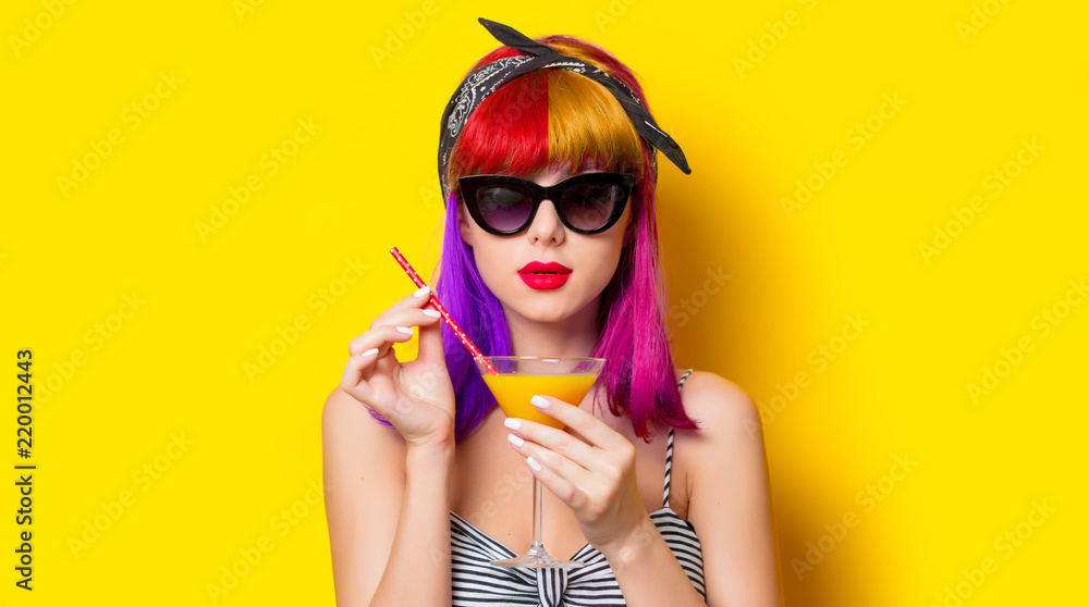 Fototapeta Young girl with purple hair holding lemonade cocktail on yellow background