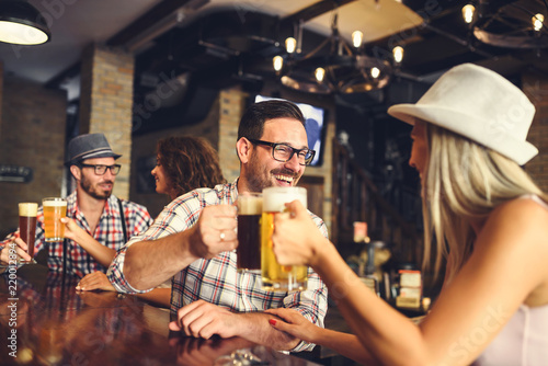 Fotografie, Obraz  Young cheerful people in the beer pub drinking and having good time