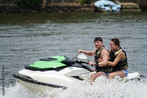 Poster Nautique motorise Happy young couple enjoying and having fun riding on a jet ski. Tropical coast of Sri Lanka