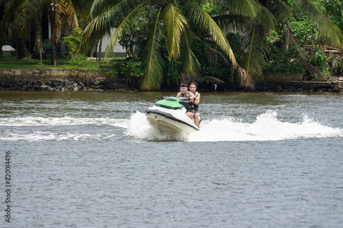 Poster Nautique motorise Happy young couple enjoying and having fun riding on a jet ski. Tropical coast of Sri Lanka