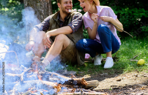 Camping activity. Couple in love camping forest eating roasted marshmallows. Roasting marshmallows popular group activity around bonfire. Couple eat roasted marshmallows snack nature background