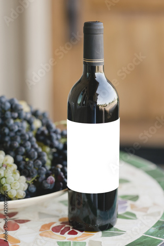 Bottle of red wine with a blank label on a table with fresh grapes