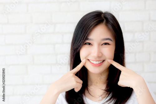Fotografia  Portrait of beautiful young asian woman happiness standing finger touch cheek on gray cement texture grunge wall brick background, businesswoman is a smiling on concrete, business people concept