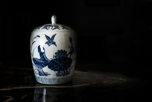 Antique Chinese Porcelain Jar In An Auction Against A Black Background. Empty Copy Space For Editor's Text.