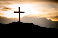 The Silhouette Cross Standing On Meadow Sunset And Flare Background.Cross On A Hill As The Morning Sun Comes Up For The Day.The Cross Symbol For Jesus Christ. Christianity, Religious, Faith, Jesus .