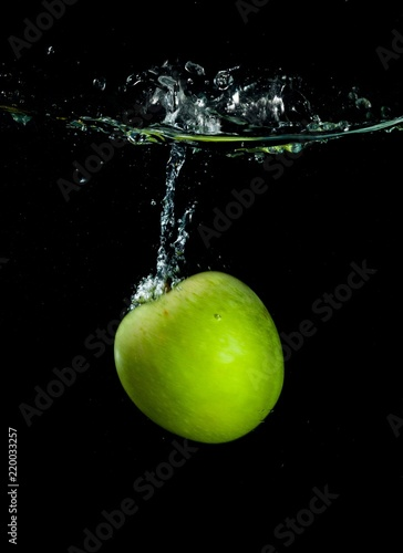 Green Apple in Water on Black Background