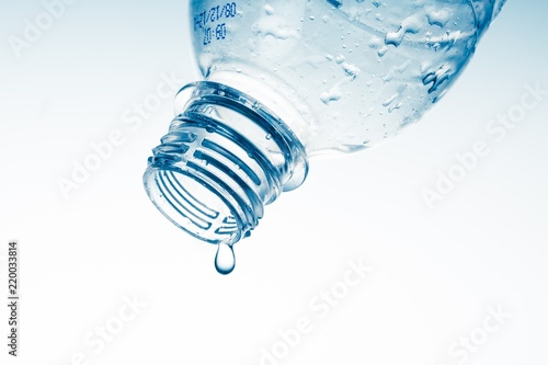 Water Drop Pouring out of Plastic Bottle on the Light Blue