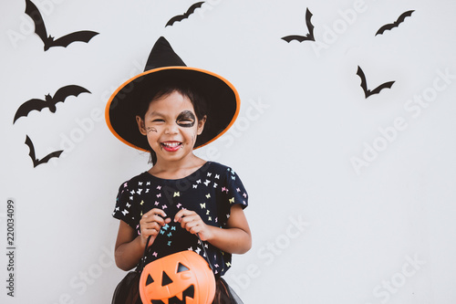 Fotografie, Obraz  Happy asian little child girl in costumes and makeup having fun on Halloween cel