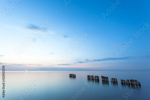 Photographie  smooth sea surface and breakwaters in blue twilight on long exposure