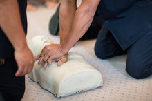 CPR Training Using And An AED And Bag Mask Valve On An Adult Training Manikin.  First Aid Cardiopulmonary Resuscitation Course Using Automated External Defibrillator Device, AED.