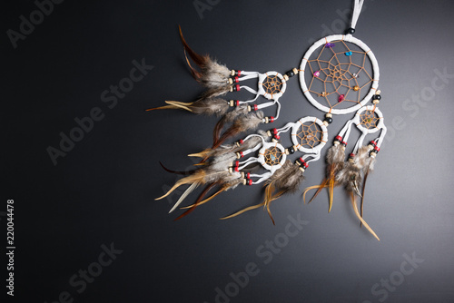 Fototapeta Dream catcher with feathers threads and beads rope hanging spiritual folk american native indian amulet isolated on black background