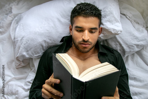 Man in bed with open shirt and pecs reading hardback book Canvas Print