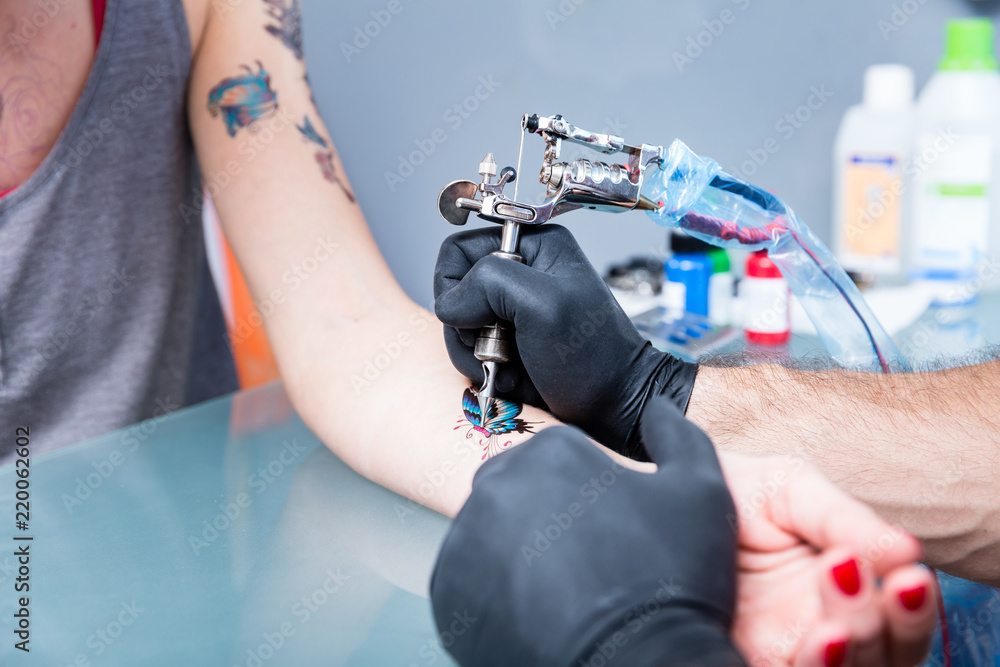 Fototapeta Close-up of the hands of a skilled tattoo artist wearing black gloves while setting a sterile machine for tattooing in a modern studio