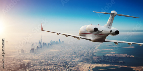 Luxury private jetliner flying above Dubai city, UAE.