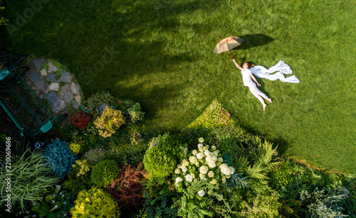 Photo  girl in the garden with an umbrella, top view