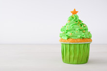 New Year Or Christmas Green Cupcake With Whipped Cream, Decorated With Christmas Tree, Gold Confectionery Balls And Star On White Wood Table.