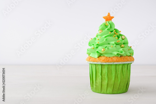 New year or christmas green cupcake with whipped cream, decorated with christmas tree, gold confectionery balls and star on white wood table Canvas Print