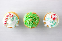 New Year Or Christmas Green Cupcakes Top View With Whipped Cream, Decorated With A Christmas Tree, Candy Cane, A Snowflake, A Red Box, Silver And Gold Confectionery Balls On White Wood Table.