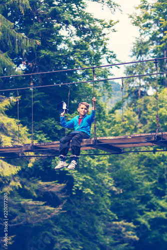 Small boy sits on a suspension bridge and dreaming