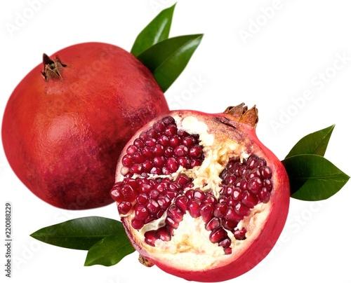 Fresh pomegranates with leaves isolated on white background