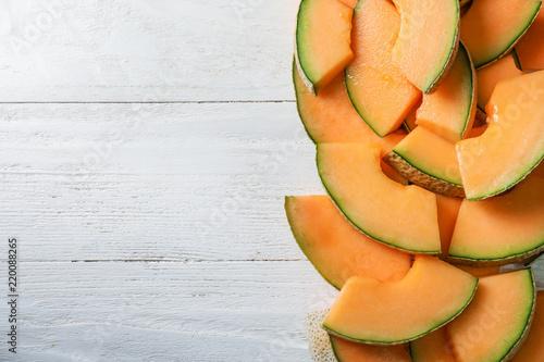 Pieces of tasty ripe melon on wooden table Fototapeta