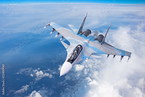 Combat fighter jet on a military mission with weapons - rockets, bombs, weapons on wings flies high in the sky above the clouds Fototapeta