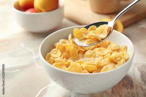 Eating of healthy cornflakes with milk from bowl on table, closeup Fotobehang