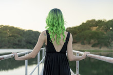 Back View Of Young Woman With Dyed Green Hair Standing On A Footbridge At Lake
