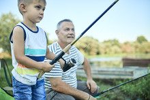 Little Boy Fishing Together With His Grandfather At Lakeshore
