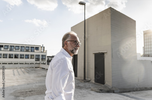 Mature man standing on roof of a high-rise building