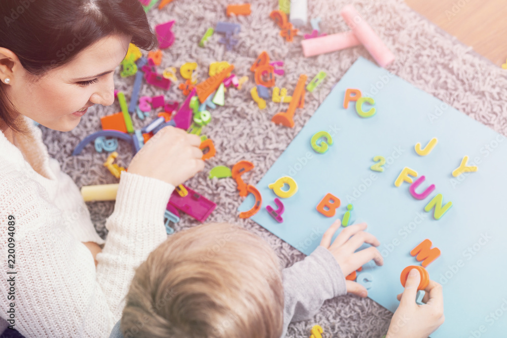 Fototapeta Boy learning letters and practising pronunciation during session with speech therapist