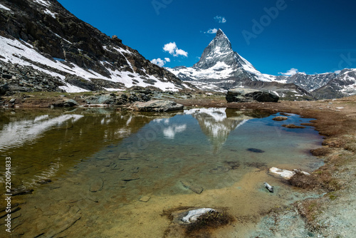 Poster Reflexion Scenic view of Matterhorn and its reflection on Riffelsee, an alpine lake of Riffelhorn in Zermatt, Switzerland.