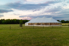 A Marquee Set Up In A Field In The Evening