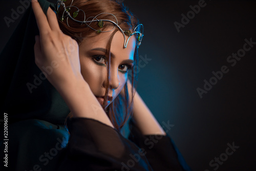 Canvas Print Pretty elf girl tighting green hood on dark background, looking at camera