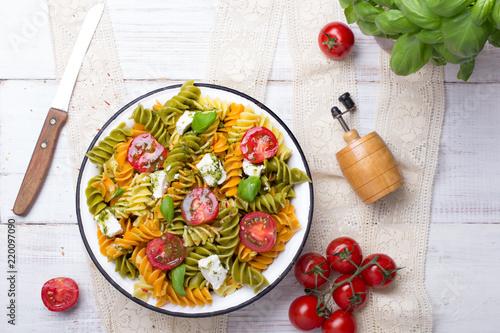 Fototapeta Kuchnia włoska - Sałatka z kolorowego makaronu, pomidorów koktajlowych, sera feta i świeżej bazylii na białym drewnianym tle. obraz