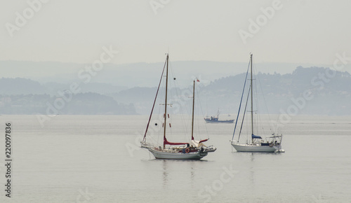 Two sailing boats in clam waters