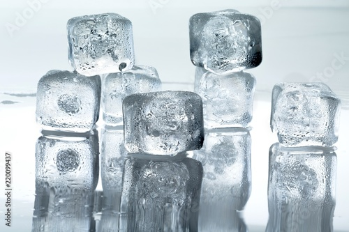 Square ice cubes stacked on a reflective surface