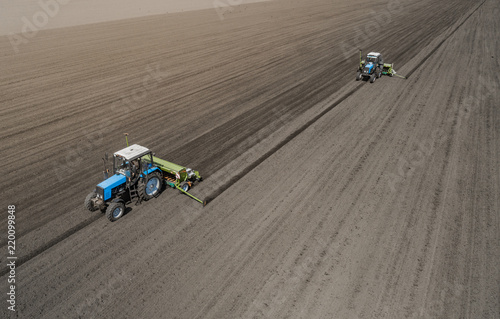 Fotografie, Obraz  Aerial view of two blue tractors plows the earth in field on a summer day against a black earth background