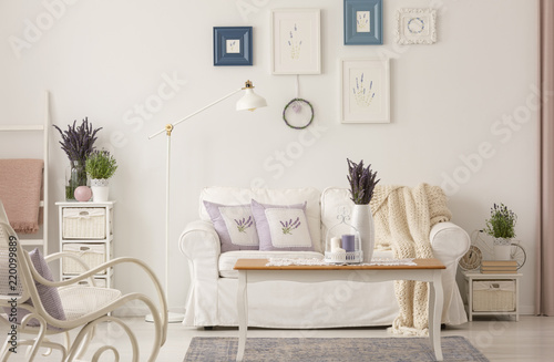 Real photo of white living room interior with fresh lavender, posters on wall, coffee table with candles and couch with cushions
