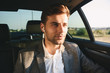 Portrait of handsome businesslike man wearing suit and earpod back sitting while riding in car