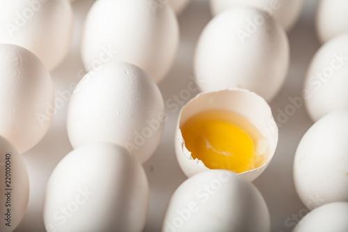 Single Cracked Egg Amongst Many Intact Eggs Close-up
