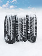 Three snowy winter tyres in front of blue sky