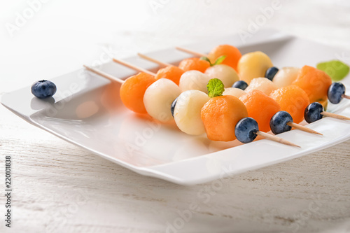 Fotografia Plate with tasty melon balls on light wooden table