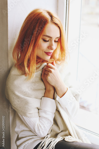 24195d6c500db Beautiful redhead young woman with red lipstick on lips sitting by the  window of coffee shop, ...