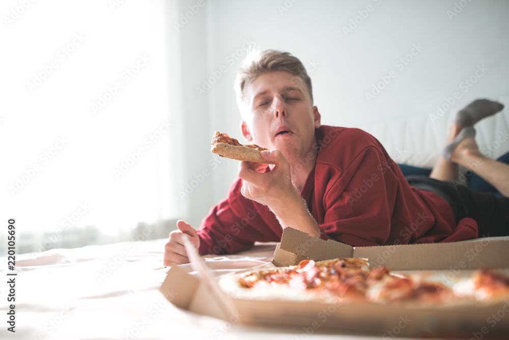 Fototapety, obrazy: Happy young man lying home on a sofa with a box of pizza, bites a piece of pizza with his eyes closed and gets pleasure. Teen is home to the bed and eats a delicious pizza. Copyspace