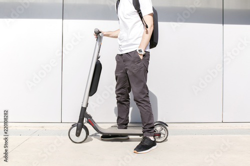 Young man in casual wear on electric scooter on city street