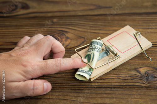 Fotografía  A man's hand got caught in a mousetrap with bait money dollar bills