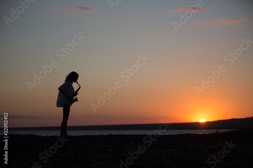 Silhouette of young sexy woman playing saxophone on the beach at sunset #220112452