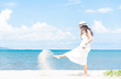 Left side of women in white dress and hat walking along the beach with blue sea and sky front view. Travel and summer conceptual.