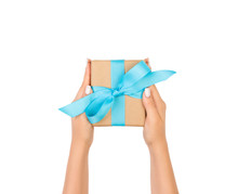 Woman Hands Holding Gift Wrapped And Decorated With Blue Bow Isolated On White